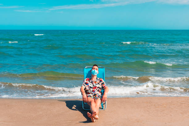 man wearing a surgical mask on the beach stock photo