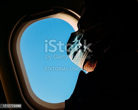 Madrid, Spain - March 13, 2020: Man wearing a surgical mask rests against an airplane window