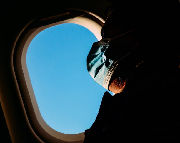 Man wearing a surgical mask rests against an airplane window stock photo