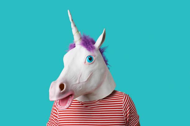 man wearing a unicorn mask stock photo