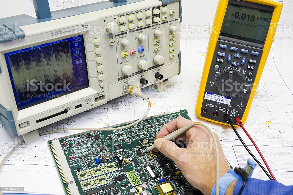 A man wearing an ESD band troubleshoots electronic circuits royalty-free stock photo