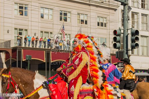 A man wearing an indian costume on a horse in the street during the Mardi Gras celebration at New Orleans Carnival, Louisiana, USA  The Mardi Gras is a great event held in New Orleans and it is visited yearly by thousands of tourists from all over the world.