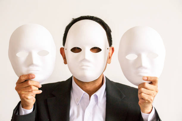 man wearing and holding masks - mask disguise stock photos and pictures