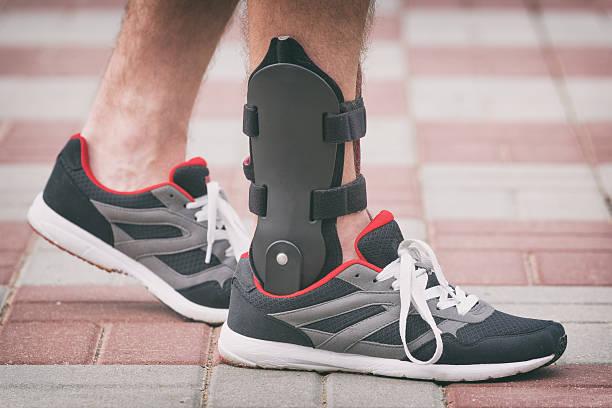 uomo indossando cavigliera ortopedica - spina dorsale umana foto e immagini stock