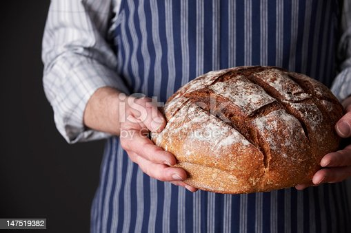 istock Man Wearing Apron Holding Freshly Baked Loaf Of Bread 147519382