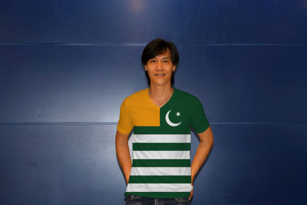 Man wearing Azad Kashmir flag on shirt and standing on the blue wall background stock photo