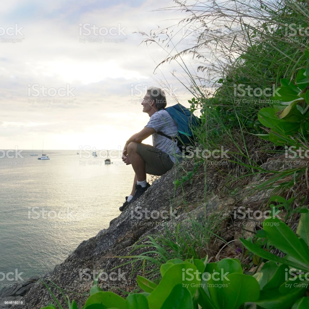 He is looking out to the sunrising over the harbour, Phuket Island