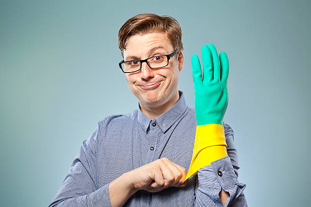 Man wearing black glasses pulling on rubber glove stock photo