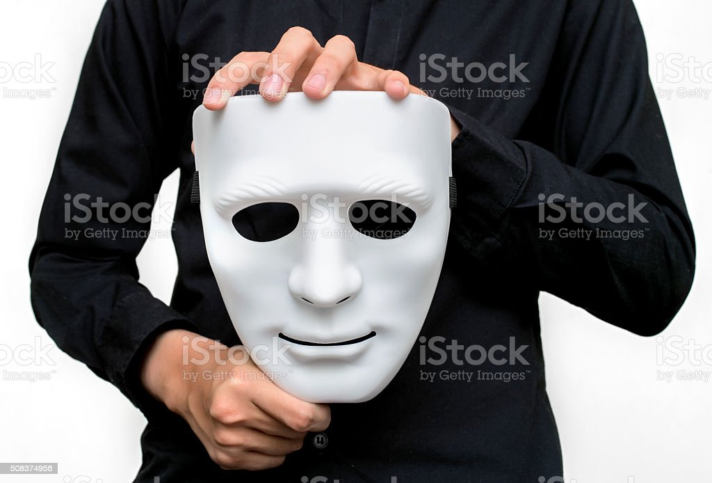 Man wearing black shirt holding a white mask stock photo