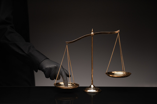 Man wearing black shirt pressing the imbalance scale on black glass desktop and black background, cheating  in a lawyer's office, Concept of injustice, espionage, partiality, law.