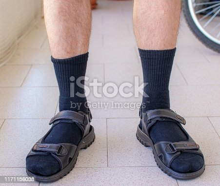 Close up shot of a man wearing black socks with sandals.