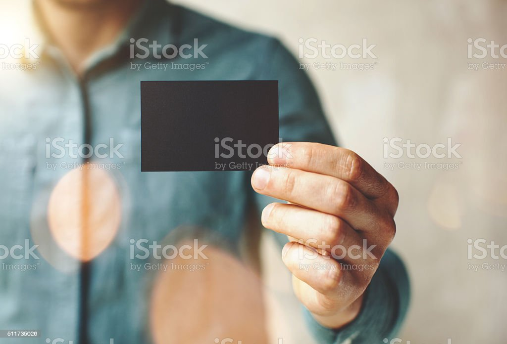Man wearing blue jeans shirt and showing blank black business stock photo