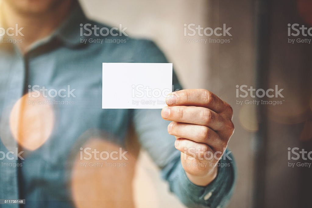 Man wearing blue jeans shirt and showing blank white business stock photo