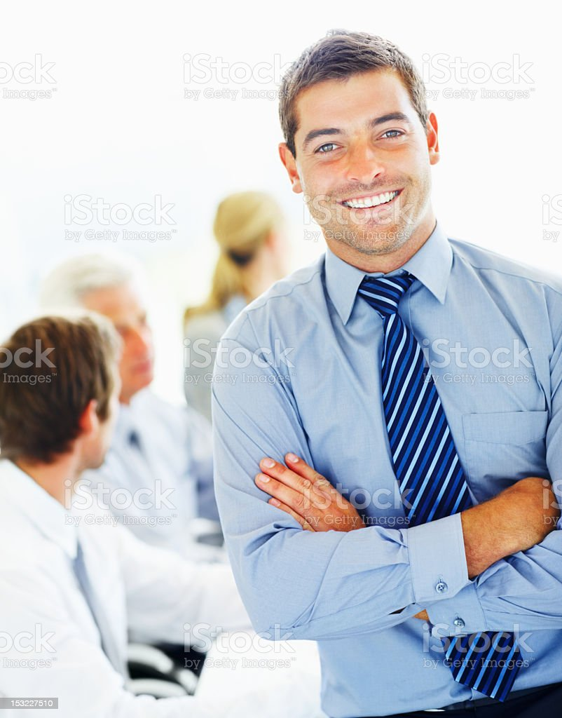 Man wearing blue shirt and tie smiling with arms folded royalty-free stock photo