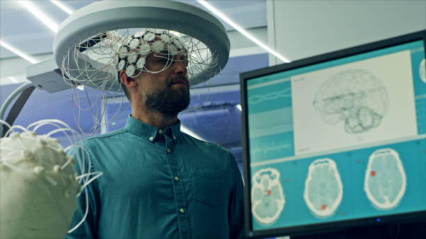Man Wearing Brainwave Scanning Headset. In modern Neurological Research Laboratory. EEG animation on monitor screen. neuroscience patient stock pictures, royalty-free photos & images