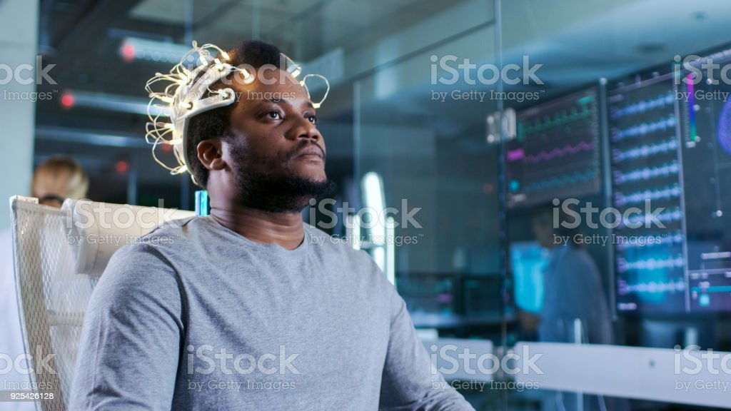 Man Wearing Brainwave Scanning Headset Sits in a Chair in the Modern Brain Study Laboratory Monitors Show EEG Reading and Brain Model. stock photo