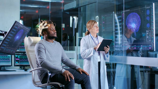 Man Wearing Brainwave Scanning Headset Sits in a Chair while Scientist with Tablet Computer Supervises Process. In the Modern Brain Study Laboratory Monitors Show EEG Reading and Brain Model. Man Wearing Brainwave Scanning Headset Sits in a Chair while Scientist with Tablet Computer Supervises Process. In the Modern Brain Study Laboratory Monitors Show EEG Reading and Brain Model. neuroscience patient stock pictures, royalty-free photos & images