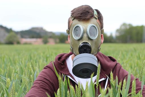 istock Man wearing breathing mask in wheat field 1006562690