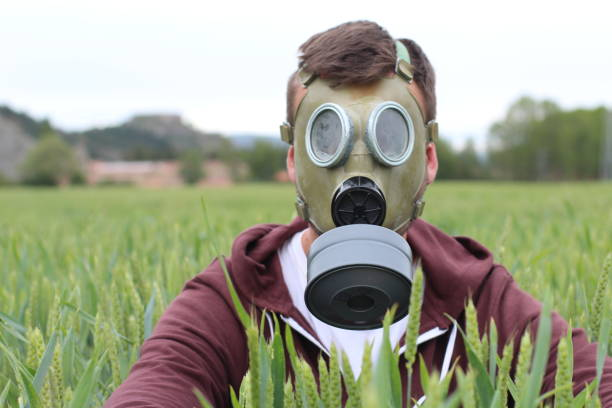 Homem com máscara de respiração em campo de trigo - foto de acervo