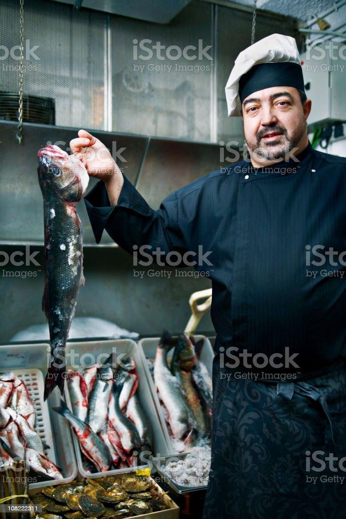 Man Wearing Chef's Uniform Displaying Fish royalty-free stock photo