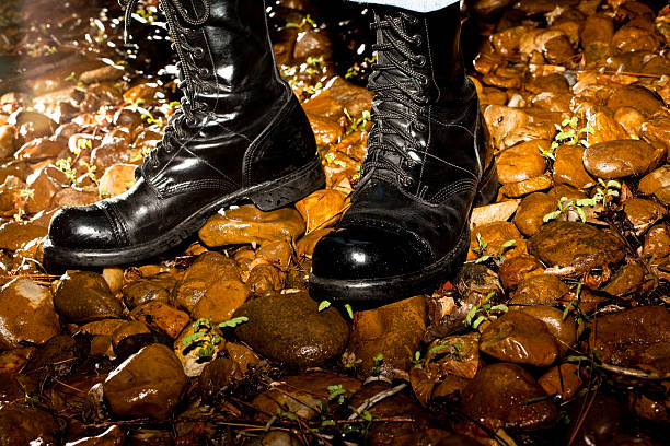 man wearing combat boots on wet rocks at night - postal worker stok fotoğraflar ve resimler