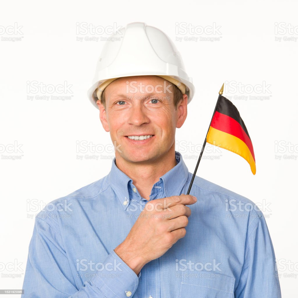 Man wearing construction hard hat holds an Germany flag royalty-free stock photo