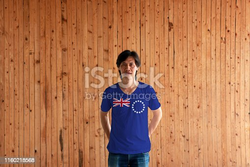 939399010 istock photo Man wearing Cook Islands flag color of shirt and standing with crossed behind the back hands on the wooden wall background. 1160218568