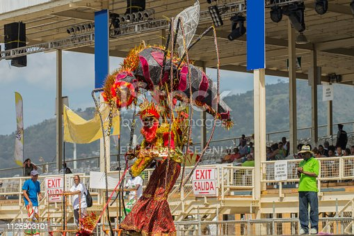 A man wearing costumes dancing at the sambadrome during the Carnival celebration at Port of Spain, Trinidad and Tobago. This is a very famous celebration in the island, visited by thousands of tourists from all over the world who enjoy music and the joy of carnival.