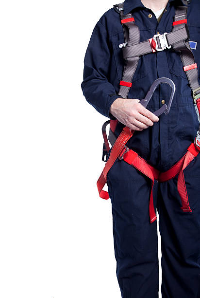 man wearing coveralls and fall protection equipment worker wearing blue coveralls and a fall protection harness and lanyard for work at heights safety harness stock pictures, royalty-free photos & images