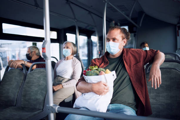 Man wearing covid mask sitting inside bus holding shopping bag stock photo