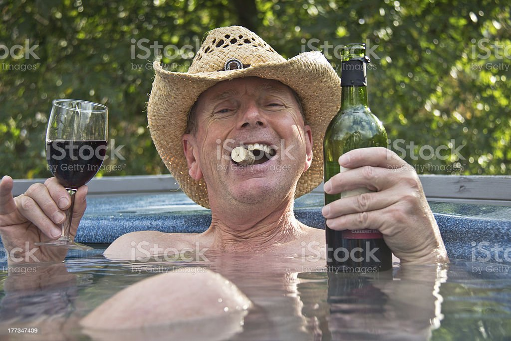 Man wearing cowboy hat sitting in hot tub with wine. stock photo