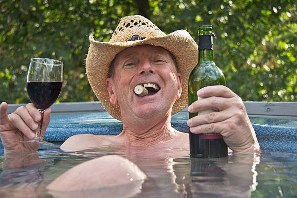 Usando sombrero de vaquero hombre sentado en la piscina de hidromasaje con vino. - foto de stock