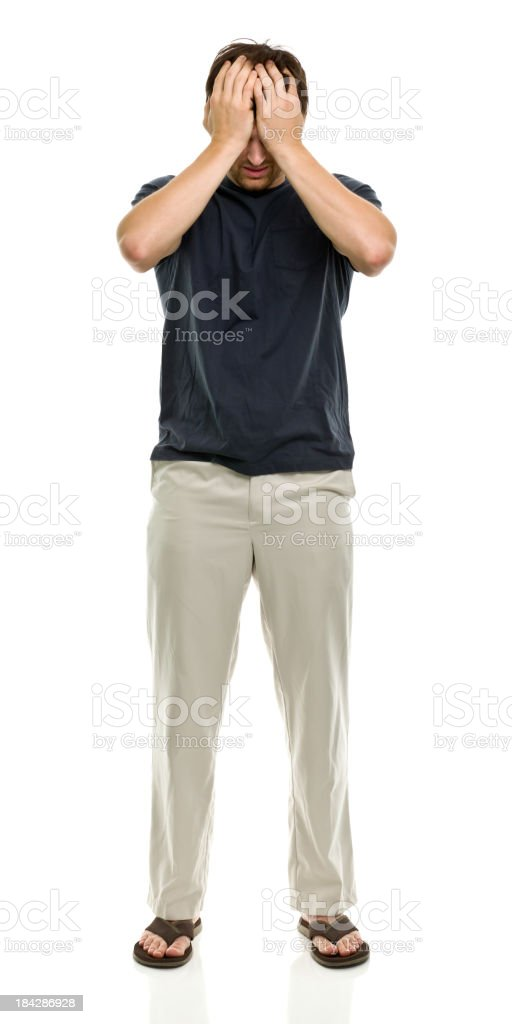 Man wearing cream trousers and flip flops with head in hands stock photo