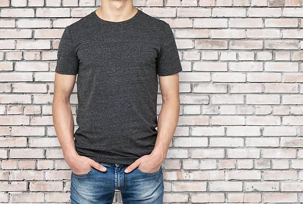 Man wearing dark grey t-shirt, brick wallbackground. Man wearing dark grey t-shirt, brick wallbackground. Hands in the pockets. chest torso stock pictures, royalty-free photos & images