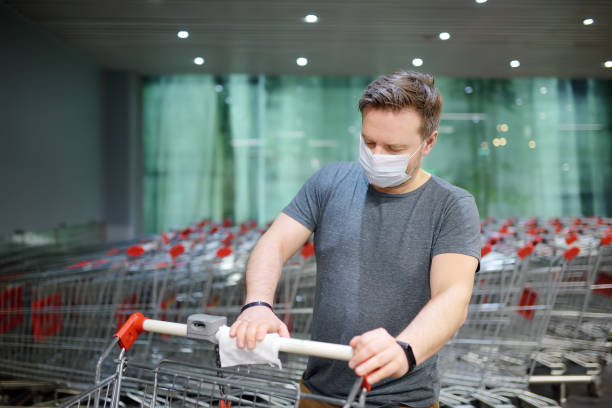 Man wearing disposable medical face mask wipes the shopping cart handle with a disinfecting cloth in supermarket. Safety during coronavirus outbreak. stock photo