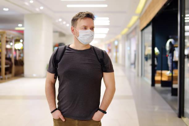 Man wearing disposable medical mask in airport or supermarket during coronavirus pneumonia outbreak stock photo