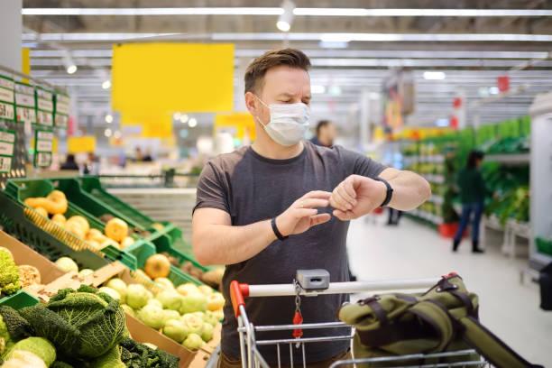 Man wearing disposable medical mask shopping in supermarket during coronavirus pneumonia outbreak stock photo