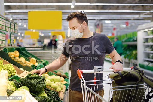 Man wearing disposable medical mask shopping in supermarket during coronavirus pneumonia outbreak. Protection and prevent measures while epidemic time.