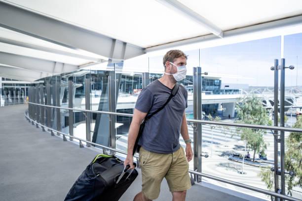 Mann trägt Gesichtsmaske am Flughafen, der vom Coronavirus-Reiseverbot und flugaus ausgesetzt ist. Annullierungen von internationalen Reisen zur Seuchenbekämpfung und zur Verhütung der COVID-19-Ausbruchspandemie. – Foto