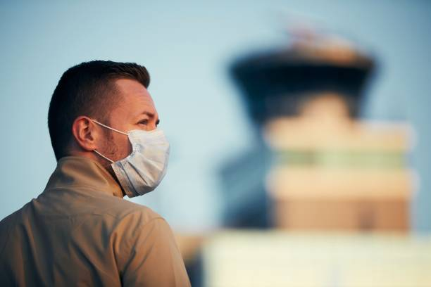 Man wearing face mask at airport stock photo