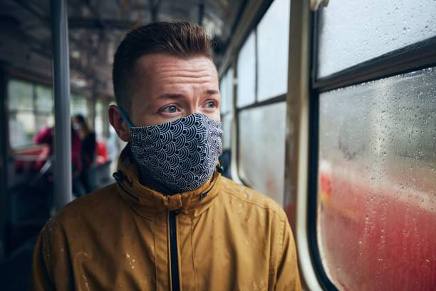 Man wearing face mask in public transportation stock photo