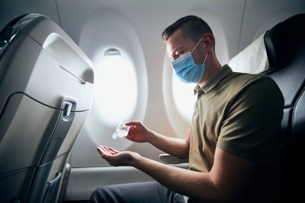 Man wearing face mask inside airplane stock photo