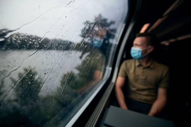Man wearing face mask inside train stock photo