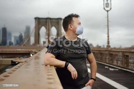 Man wearing protection face mask on famous brooklyn bridge in rainy summer day. Landmarks of New York, USA. States lifting virus lockdown orders. Social distancing remain to keep virus from resurging.