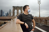 istock Man wearing face mask on famous brooklyn bridge in rainy summer day. States lifting virus lockdown orders. Social distancing restrictions will remain to keep the virus from resurging. 1230581534