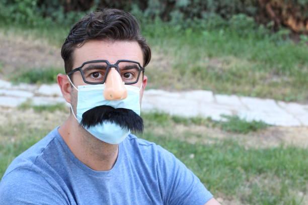 hombre con nariz falsa, anteojos, bigote y epp - halloween covid fotografías e imágenes de stock