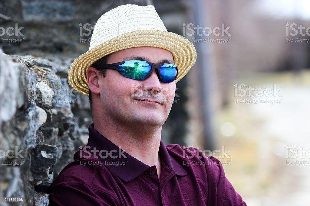 Homem usando o Fedora chapéu e óculos de sol Poses contra o Muro de Pedra  foto 835ebc05e3