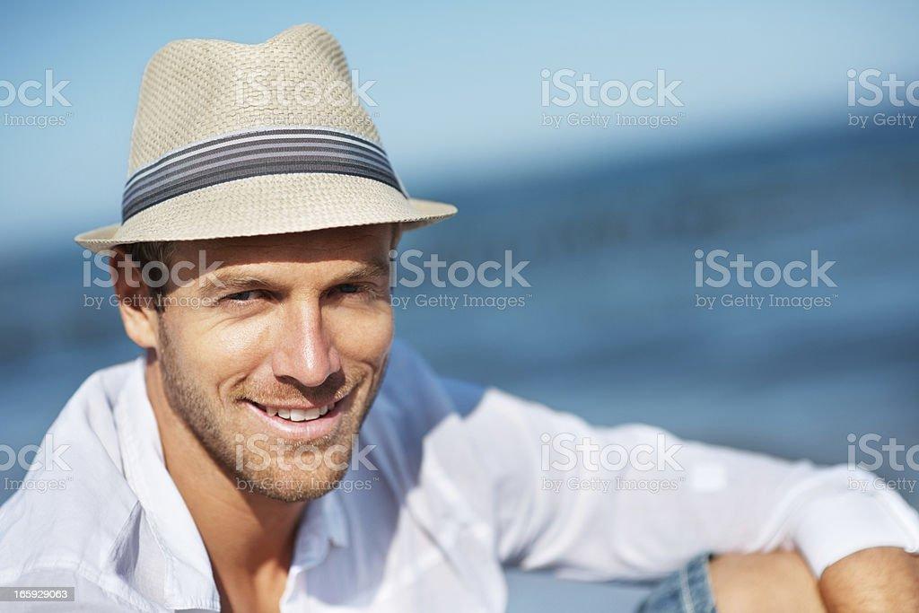Man wearing fedora hat on the beach stock photo