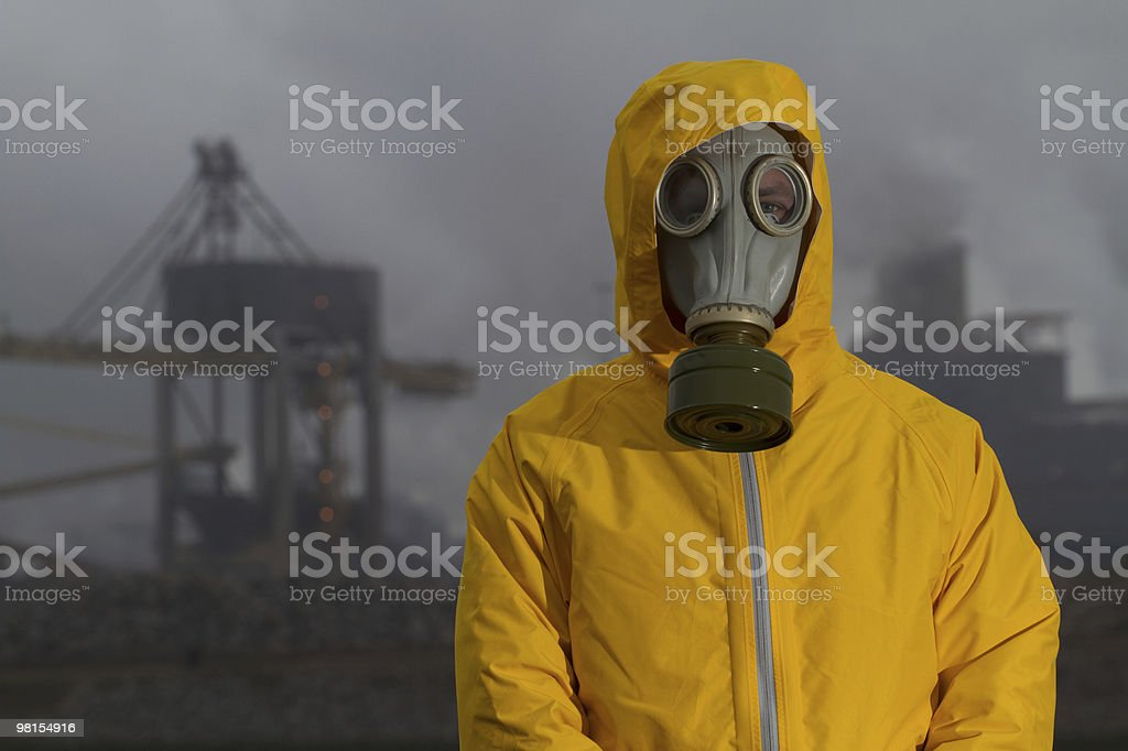 Man wearing gas mask standing infront of factory. Frontal shot. royalty-free stock photo