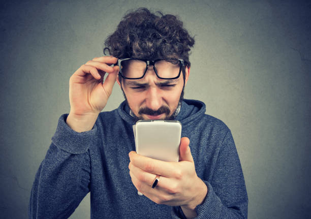 man wearing glasses having trouble seeing cell phone message stock photo